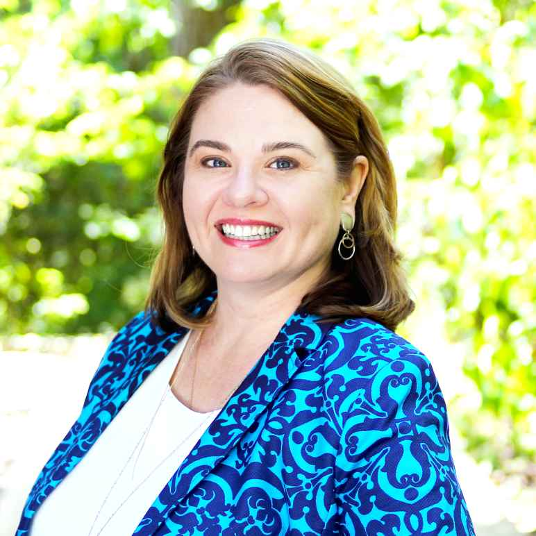 Jenny Heitkemper wearing blue patterned blazer and white blouse in front of bright, outdoor, leafy background.