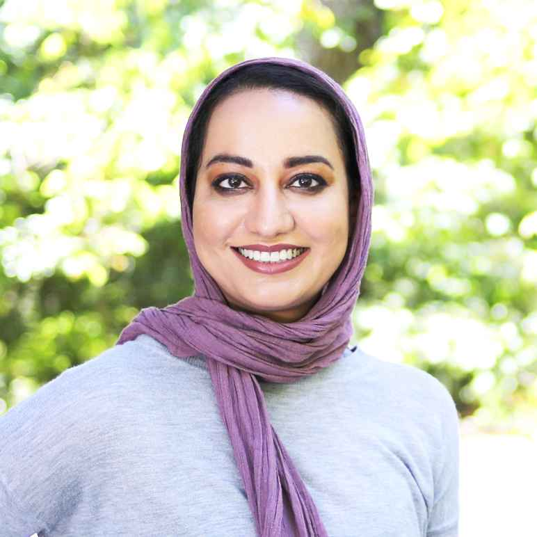 Soha Saiyed wearing gray sweater and purple head scarf, standing in front of bright, outdoor, leafy background.